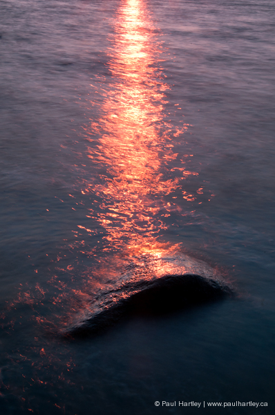 reflection of sun in water with rock