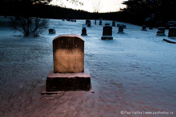 warm lit grave stone in winter