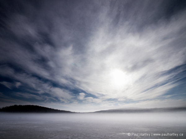 Bright sky and mist on frozen lake
