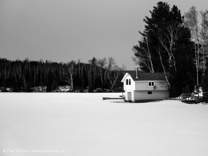 Black and white boathouse in winter