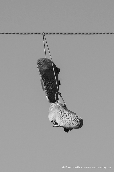 Pair of shoes hanging from wire