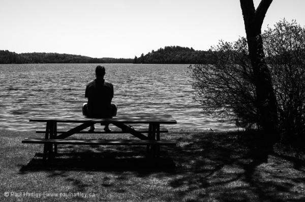 Man sitting by a lake
