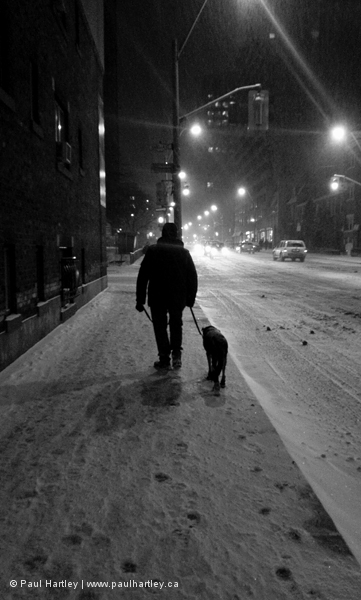 Man and his dog on snow covered sidewalk