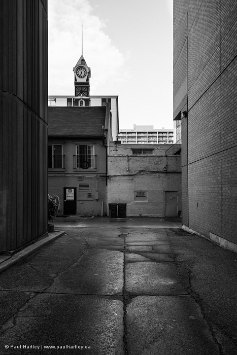 view of clock from an alley