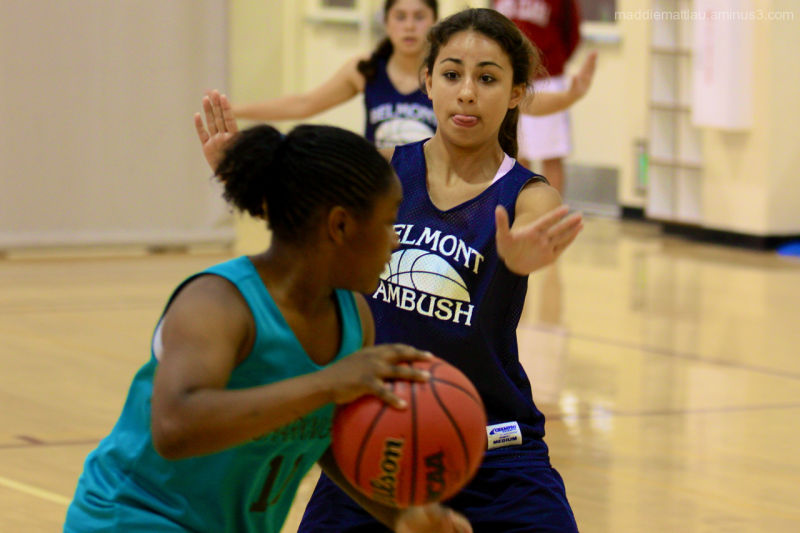 A girl plays defense in basketball