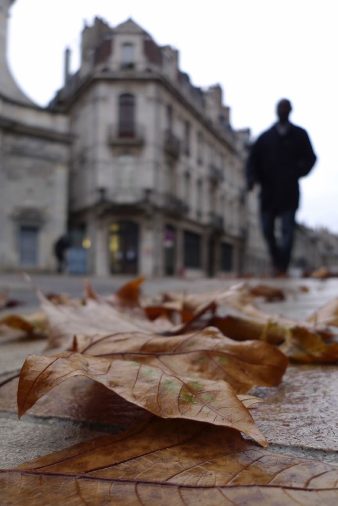 A black man pass by walking on leaves
