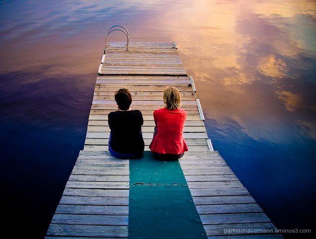 Two women celebrate friendship on dock at Sunset