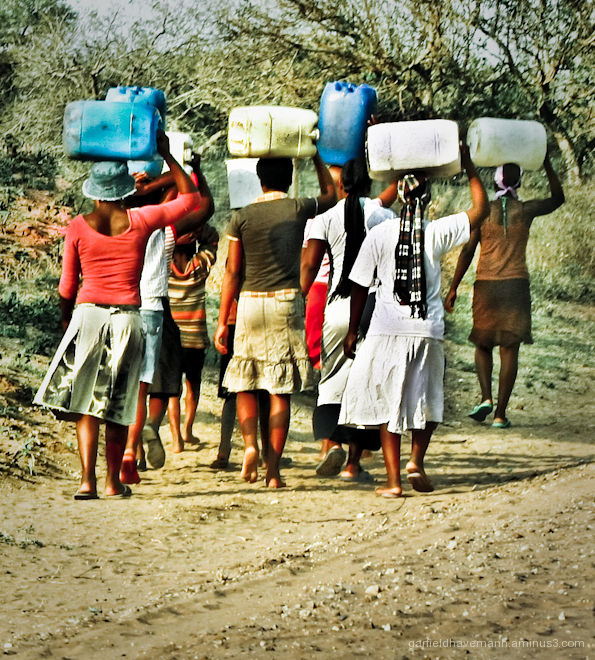Women carrying water containers on their heads