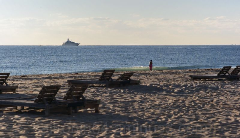 woman watching yacht from the beach