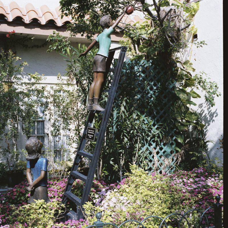 Sculpture children on ladder in the garden
