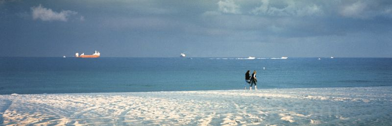 Two walkers on Fort Lauderdale beach with ship