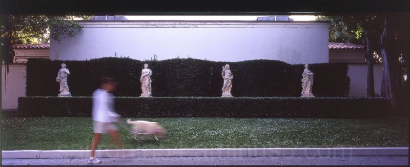 woman walking dog in front of four statues