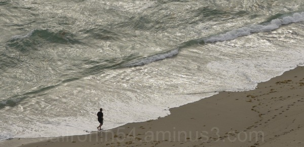 Jogger at dawn on Palm Beach along the waves