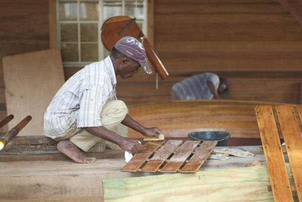 Craftsman sanding boat parts for varnish, Antigua