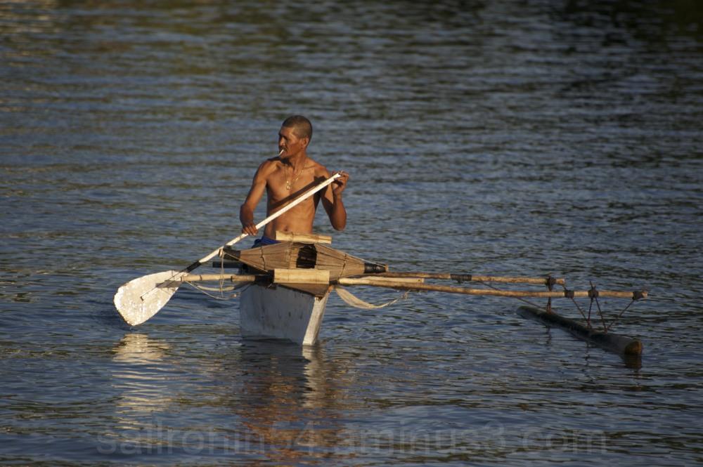 Tahitian fisherman in outrigger canoe