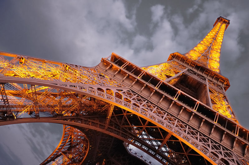Eiffel Tower at dusk with lights turning on