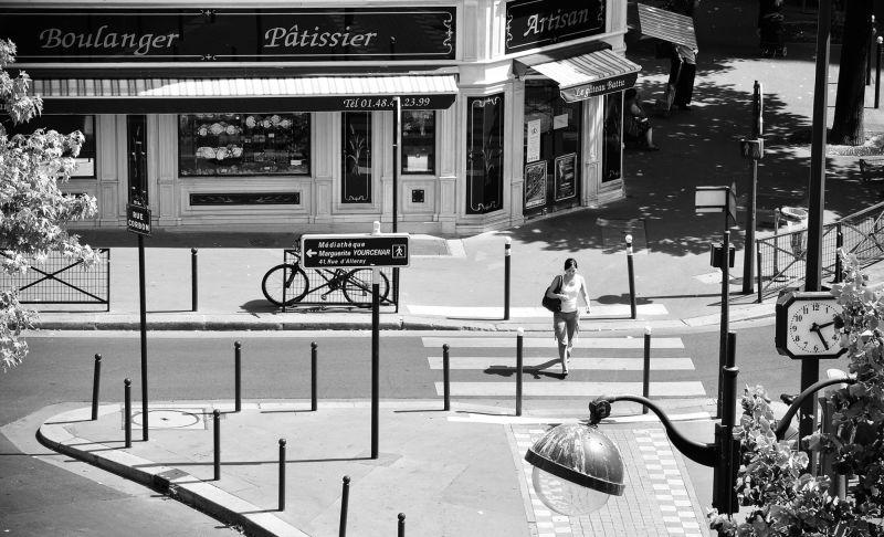 Woman crossing Rue Corbon in Paris, France