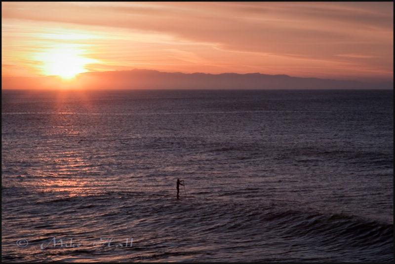 A paddle surfer in Santa Cruz greets the sunrise