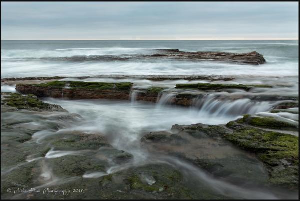 Receding wave flowing over rocks, Monterey Bay
