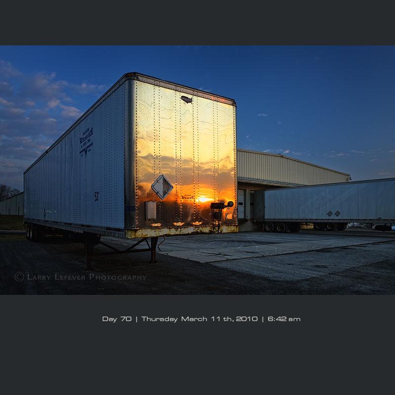 Truck trailer's bulkhead reflecting sunrise.