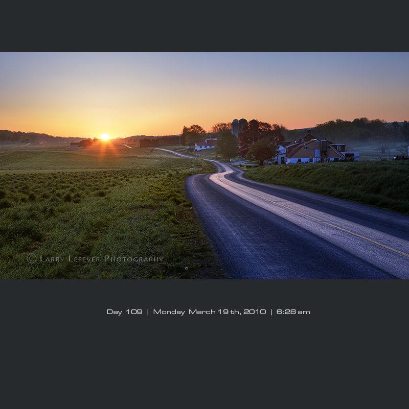 Winding road through farmland at sunrise.