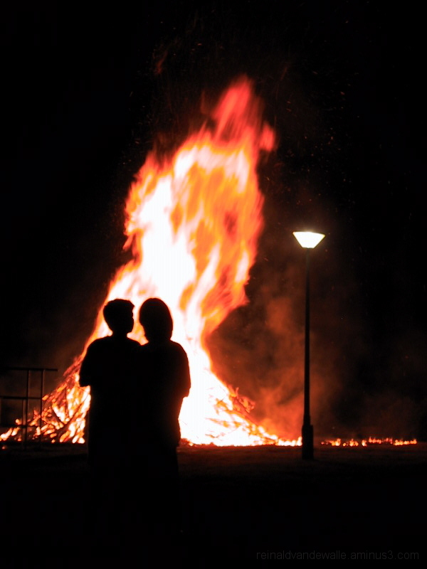 A couple in the light of the campfire.