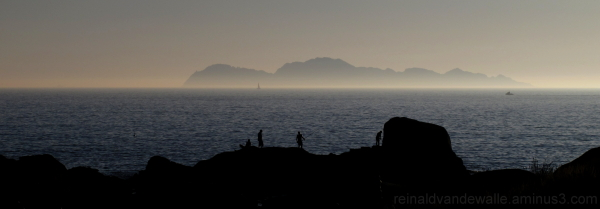 Fishermen and an island in the background.