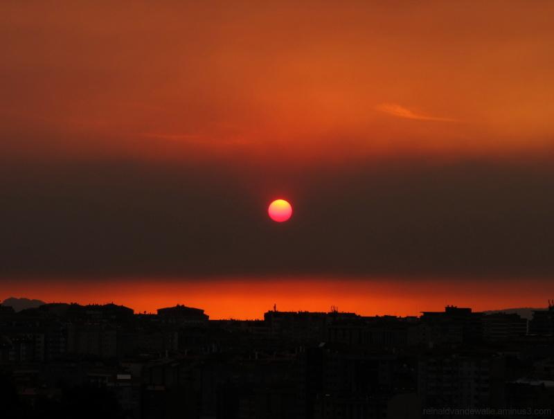Sun behind forest smoke