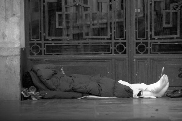 un SDF couché sur un trottoir