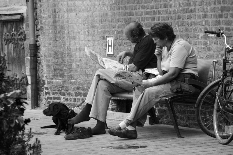 Un couple assis à l'aise sur un banc.