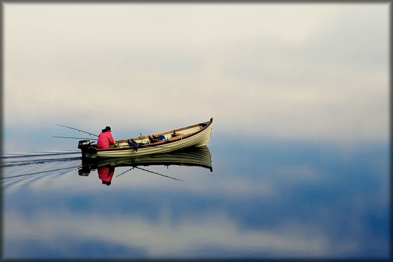 fisherman on lake with boat