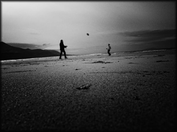 father & son playing on beach