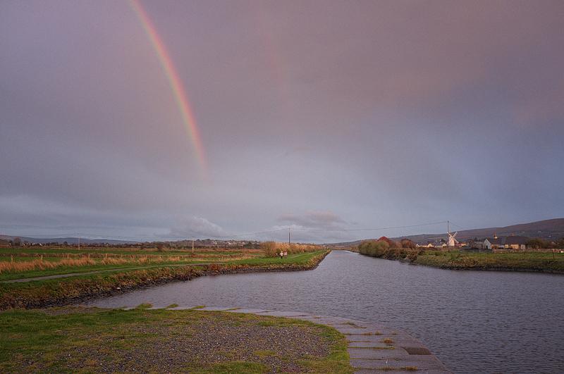 rainbow over two people walking