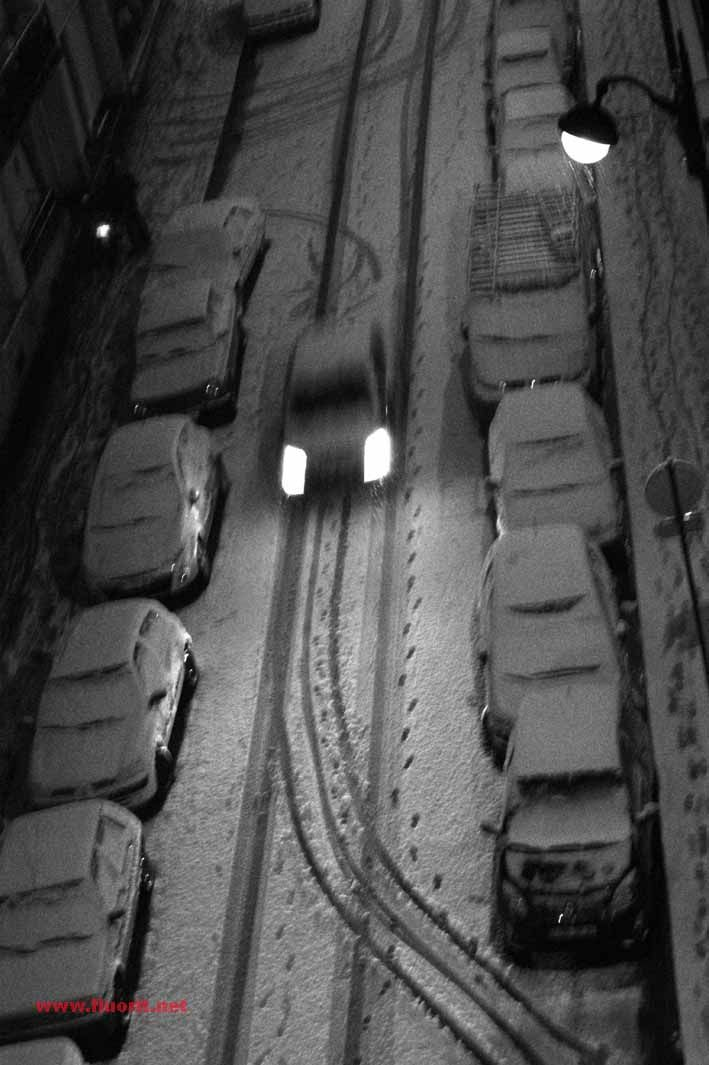 car in the middle of the snowed street at night