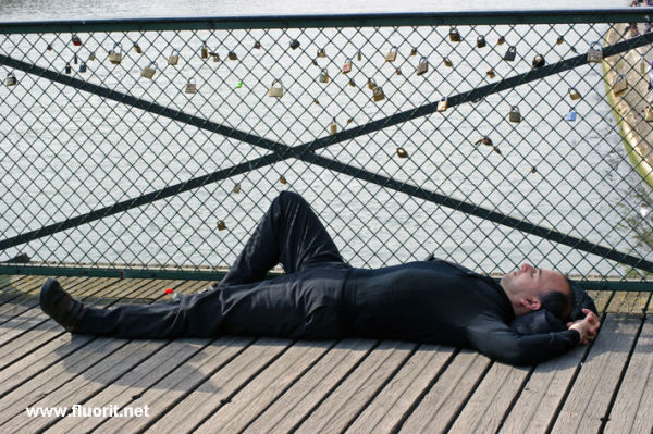 Man dressed in black sleeping on the Pont des Arts