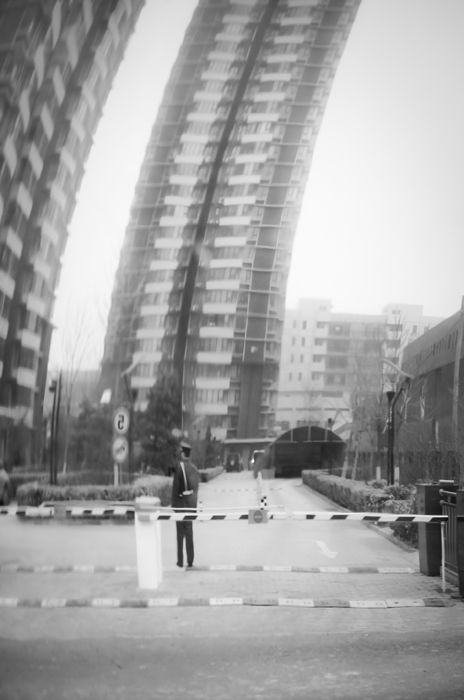 Chinese Guard in the front of complex with flats.