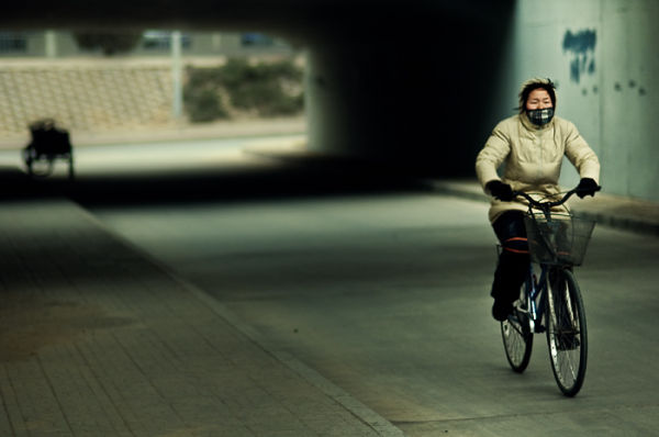 Cyclist on Beijing street, China.