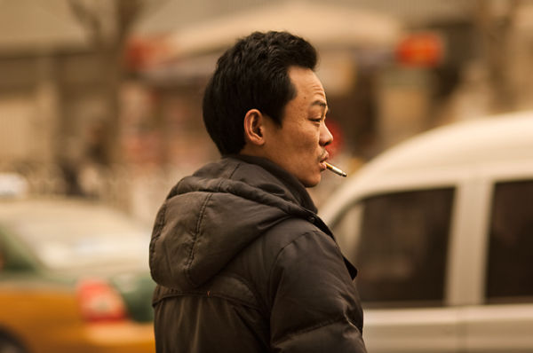 Smoking man on Beijing street. Gregory Kowalski