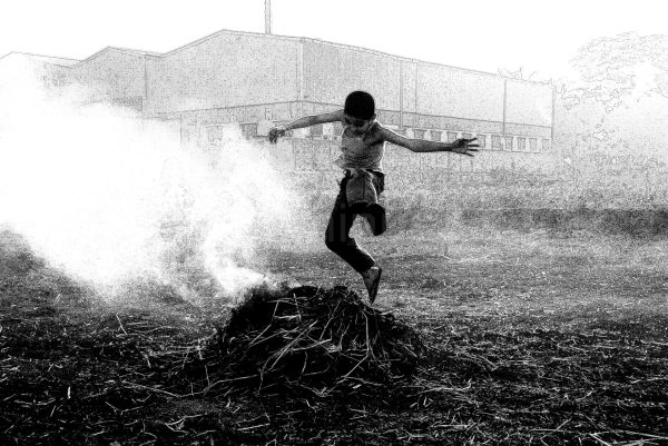 village kid jumping over leftover burning crops