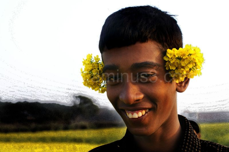 boy poses with musturd flower