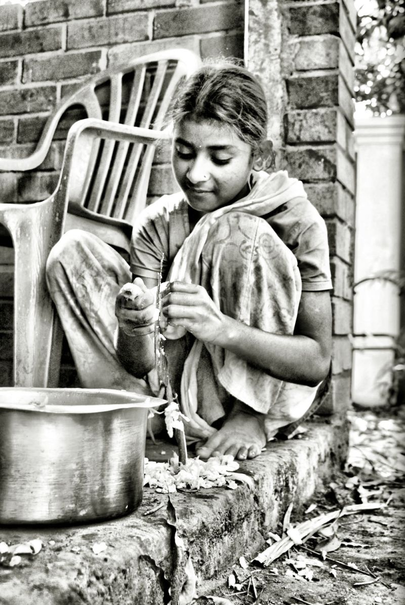 young girl cutting chicken