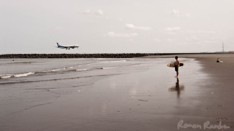 A surfer preparing for surfing while a plane lands