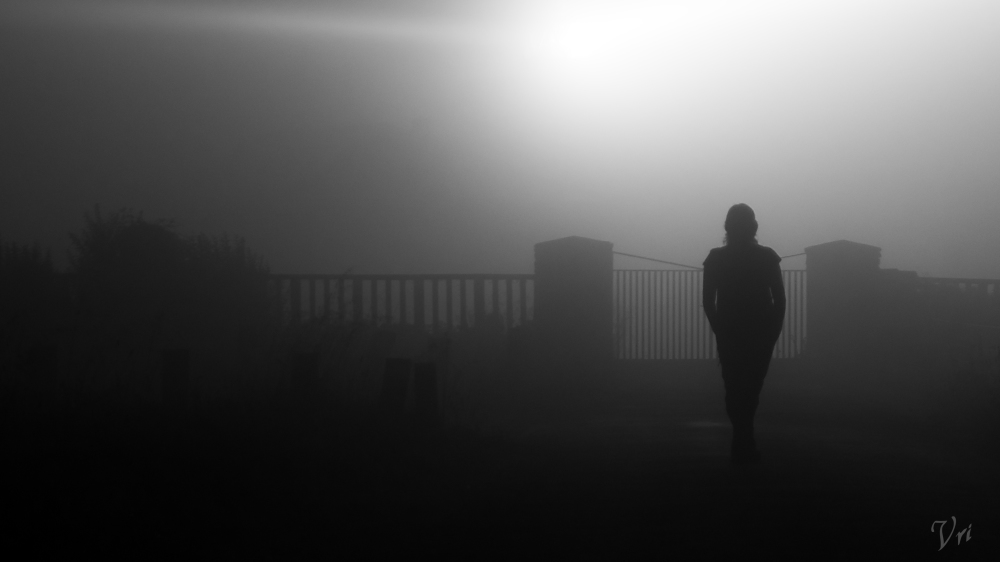 A girl walks in a foggy night.