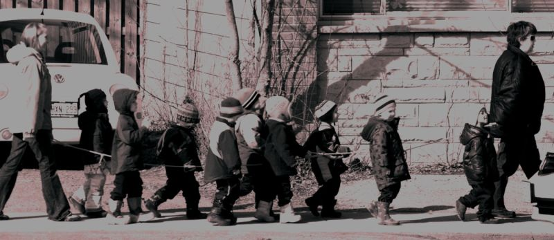 A group of children being led around with a rope