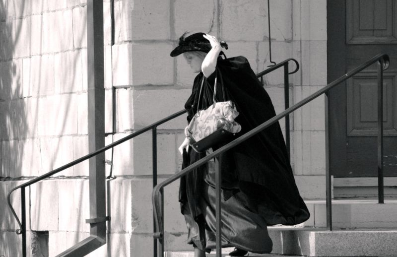 A lady fixing her hat as she descends a staircase