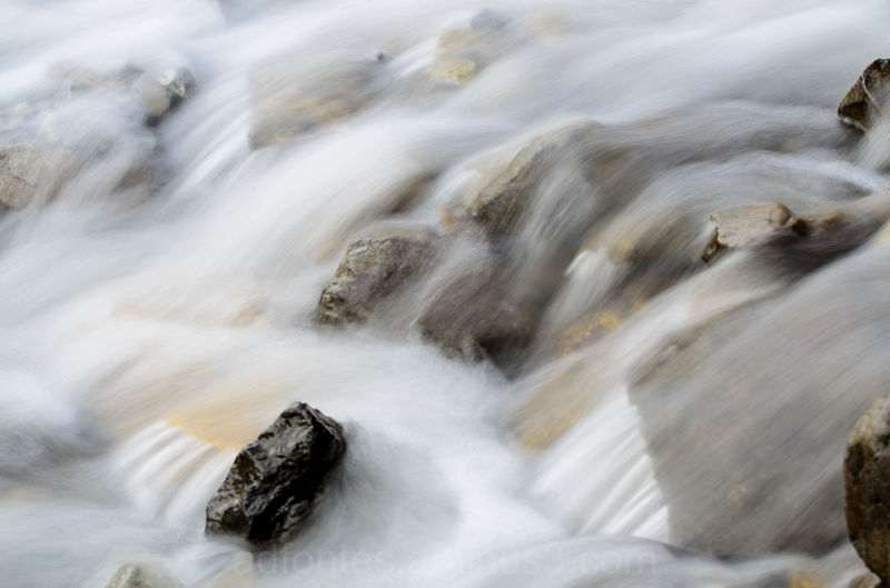Silky Water Flowing Over Rocks in River in Winter
