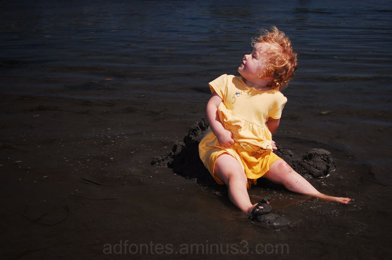 Baby in Yellow Dress Sitting in Beach Mud in BC