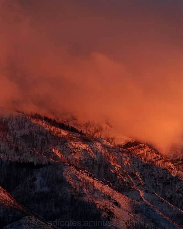 Vivid red clouds above snowy mountains at sunset