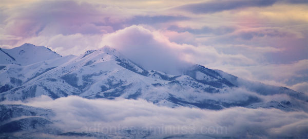 Colorful cloudy sunset over snow capped mountains