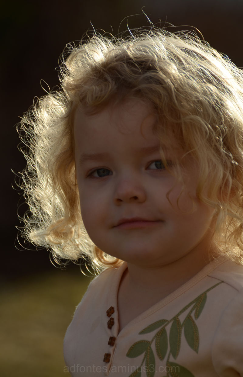 Portrait of a girl with backlit golden curly hair.
